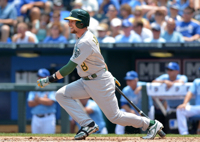 Jul 7, 2013; Kansas City, MO, USA; Oakland Athletics shortstop Jed Lowrie (8) connects for a one run single in the second inning of the game against the Oakland Athletics at Kauffman Stadium. Mandatory Credit: Denny Medley-USA TODAY Sports
