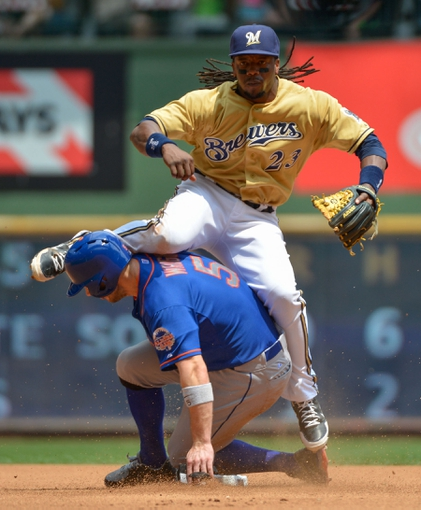 Jul 7, 2013; Milwaukee, WI, USA;  Milwaukee Brewers second baseman Rickie Weeks (23) completes a double play after forcing out New York Mets third baseman David Wright (5) at 2nd base in the 3rd inning at Miller Park. Mandatory Credit: Benny Sieu-USA TODAY Sports