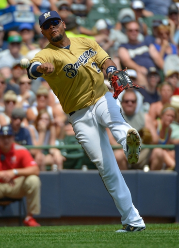 Jul 7, 2013; Milwaukee, WI, USA;  Milwaukee Brewers third baseman Juan Francisco makes a throwing error after an infield hit by New York Mets left fielder Andrew Brown (not pictured) allowing a run to score in the 4th inning at Miller Park. Mandatory Credit: Benny Sieu-USA TODAY Sports