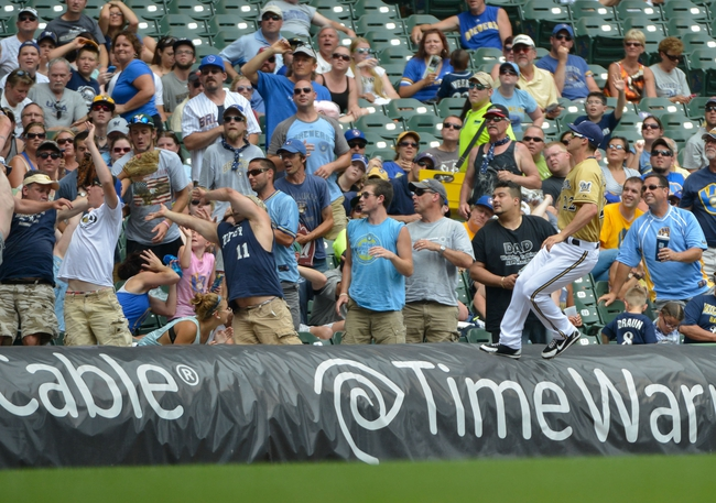 Jul 7, 2013; Milwaukee, WI, USA;  Milwaukee Brewers left fielder Logan Schafer (22) jumps on top of the rain tarp while chasing a foul ball by New York Mets shortstop Omar Quintanilla in the 5th inning at Miller Park. Mandatory Credit: Benny Sieu-USA TODAY Sports