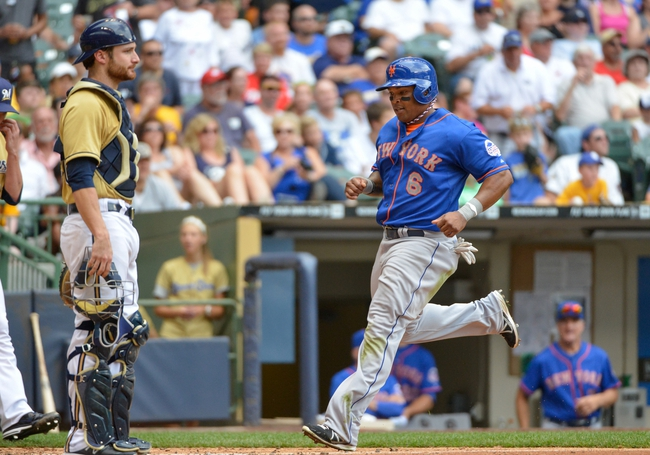 Jul 7, 2013; Milwaukee, WI, USA; New York Mets right fielder Marlon Byrd scores in front of Milwaukee Brewers catcher Jonathan Lucroy on a double by first baseman Josh Satin (not pictured) in the 6th inning at Miller Park. Mandatory Credit: Benny Sieu-USA TODAY Sports