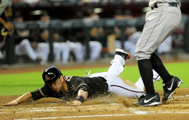 Jul 7, 2013; Phoenix, AZ, USA; Arizona Diamondbacks base runner Eric Chavez (12) slides into home plate during the second inning during a game against the Colorado Rockies at Chase Field. Eric Chavez scores on Roy Oswalt's (not pictured) wild pitch. Mandatory Credit: Jennifer Hilderbrand-USA TODAY Sports