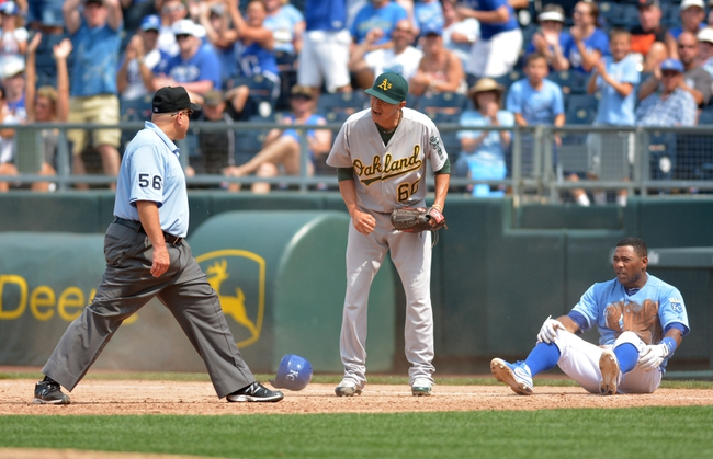 Jul 7, 2013; Kansas City, MO, USA; Oakland Athletics relief pitcher Jesse Chavez (60) argues with first base umpire Eric Cooper (56) after Cooper called Kansas City Royals shortstop Miguel Tejada (24) safe at first in the sixth inning at Kauffman Stadium. Mandatory Credit: Denny Medley-USA TODAY Sports