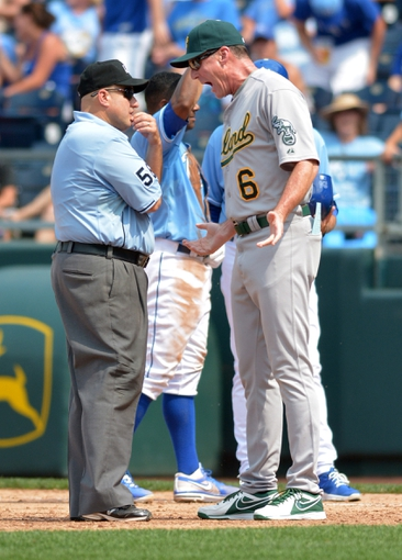 Jul 7, 2013; Kansas City, MO, USA; Oakland Athletics manager Bob Melvin (6) argues with first base umpire Eric Cooper (56) after Cooper called Kansas City Royals shortstop Miguel Tejada (24) (not pictured) safe at first in the sixth inning at Kauffman Stadium. Mandatory Credit: Denny Medley-USA TODAY Sports