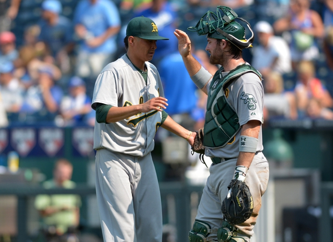 Jul 7, 2013; Kansas City, MO, USA; Oakland Athletics relief pitcher Jesse Chavez (60) is congratulated by catcher John Jaso (5) at the end of the game against the Kansas City Royals at Kauffman Stadium. Oakland won 10-4. Mandatory Credit: Denny Medley-USA TODAY Sports