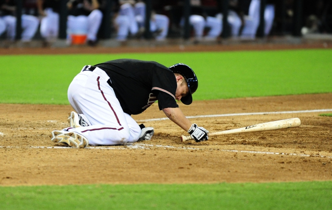 Jul 7, 2013; Phoenix, AZ, USA; Arizona Diamondbacks batter Aaron Hill (2) falls to the ground in the seventh inning during a game against the Colorado Rockies at Chase Field. Mandatory Credit: Jennifer Hilderbrand-USA TODAY Sports