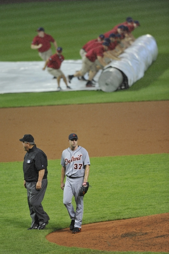 Jul 8, 2013; Cleveland, OH, USA; Detroit Tigers starting pitcher Max Scherzer (37) walks beside umpire Joe West during a rain delay in the the first inning against the Cleveland Indians at Progressive Field. Mandatory Credit: David Richard-USA TODAY Sports