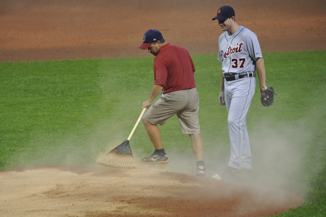 Jul 8, 2013; Cleveland, OH, USA; Cleveland Indians head groundskeeper Brandon Koehnke (left) works on the mound beside Detroit Tigers starting pitcher Max Scherzer (37) in the fourth inning at Progressive Field. Mandatory Credit: David Richard-USA TODAY Sports
