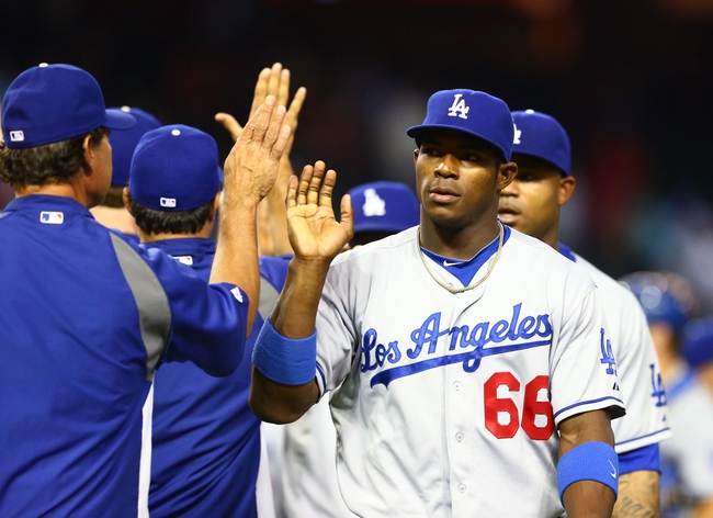 Jul. 8, 2013; Phoenix, AZ, USA: Los Angeles Dodgers outfielder Yasiel Puig (66) high fives manager Don Mattingly following the game against the Arizona Diamondbacks at Chase Field. The Dodgers defeated the Diamondbacks 6-1. Mandatory Credit: Mark J. Rebilas-USA TODAY Sports
