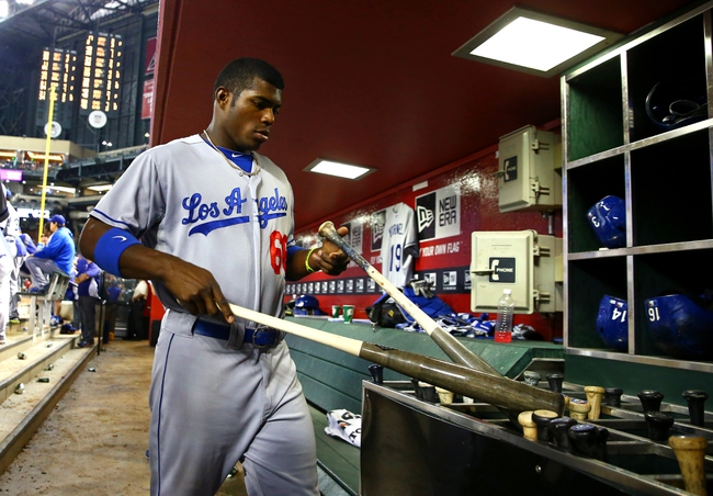 Jul. 8, 2013; Phoenix, AZ, USA: Los Angeles Dodgers outfielder Yasiel Puig grabs a bat in the dugout against the Arizona Diamondbacks at Chase Field. Mandatory Credit: Mark J. Rebilas-USA TODAY Sports