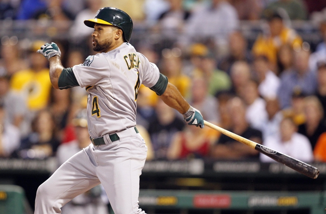 Jul 9, 2013; Pittsburgh, PA, USA; Oakland Athletics center fielder Coco Crisp (4) singles against the Pittsburgh Pirates during the first inning at PNC Park. Mandatory Credit: Charles LeClaire-USA TODAY Sports