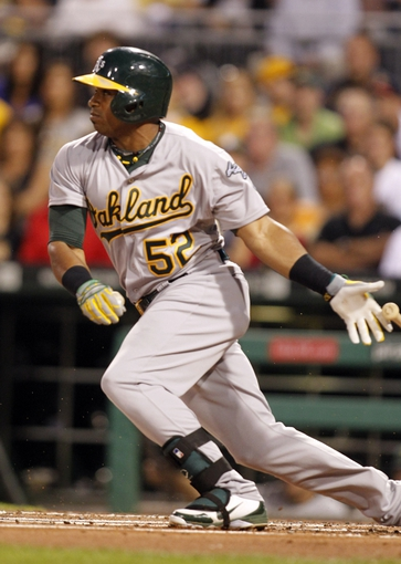 Jul 9, 2013; Pittsburgh, PA, USA; Oakland Athletics left fielder Yoenis Cespedes (52) singles against the Pittsburgh Pirates during the first inning at PNC Park. Mandatory Credit: Charles LeClaire-USA TODAY Sports