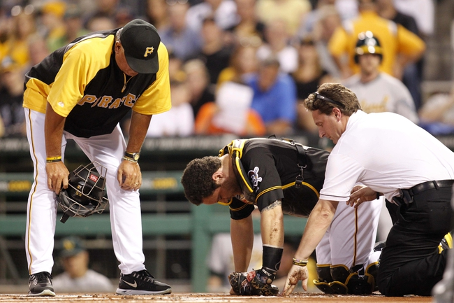 Jul 9, 2013; Pittsburgh, PA, USA; Pittsburgh Pirates manager Clint Hurdle (left) and trainer Todd Tomczyk (right) check on catcher Russell Martin (center) after Martin was hit by a foul ball against the Oakland Athletics during the first inning at PNC Park. Mandatory Credit: Charles LeClaire-USA TODAY Sports