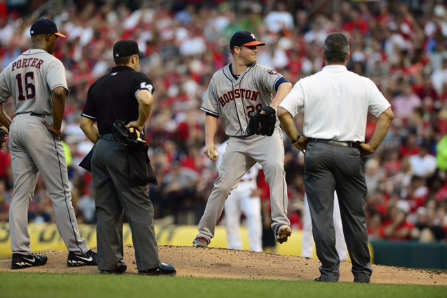 Jul 9, 2013; St. Louis, MO, USA; Houston Astros starting pitcher Bud Norris (20) throws a warm up pitch as manager Bo Porter (16) and umpire Mark Wegner (14) look on after injuring his leg during the second inning against the St. Louis Cardinals at Busch Stadium. Norris stayed in the game. Mandatory Credit: Jeff Curry-USA TODAY Sports