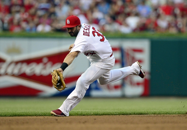 Jul 9, 2013; St. Louis, MO, USA; St. Louis Cardinals shortstop Daniel Descalso (33) fields a ground ball but can not throw out Houston Astros starting pitcher Bud Norris (not pictured) during the third inning at Busch Stadium. Mandatory Credit: Jeff Curry-USA TODAY Sports