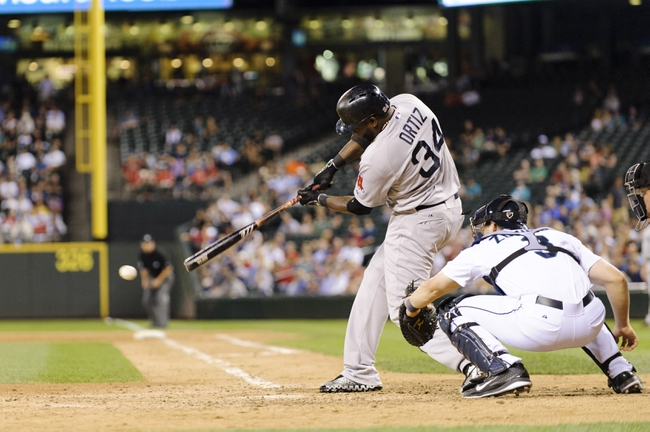 Jul 9, 2013; Seattle, WA, USA; Boston Red Sox designated hitter David Ortiz (34) hits a single against the Seattle Mariners during the 8th inning for his 4th hit of the night at Safeco Field. Mandatory Credit: Steven Bisig-USA TODAY Sports