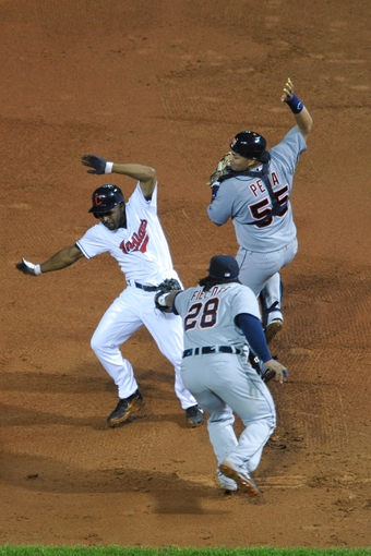 Jul 8, 2013; Cleveland, OH, USA; Cleveland Indians center fielder Michael Bourn (left) is tagged out while caught stealing second base by Detroit Tigers first baseman Prince Fielder (28) during a game at Progressive Field. Detroit won 4-2. Also in the rundown is catcher Brayan Pena (55). Mandatory Credit: David Richard-USA TODAY Sports