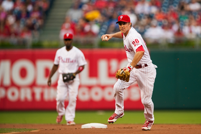Jul 10, 2013; Philadelphia, PA, USA; Philadelphia Phillies second baseman Chase Utley (26) throws to first base as shortstop Jimmy Rollins (11) watches during the first inning against the Washington Nationals at Citizens Bank Park. The Nationals defeated the Phillies 5-1. Mandatory Credit: Howard Smith-USA TODAY Sports