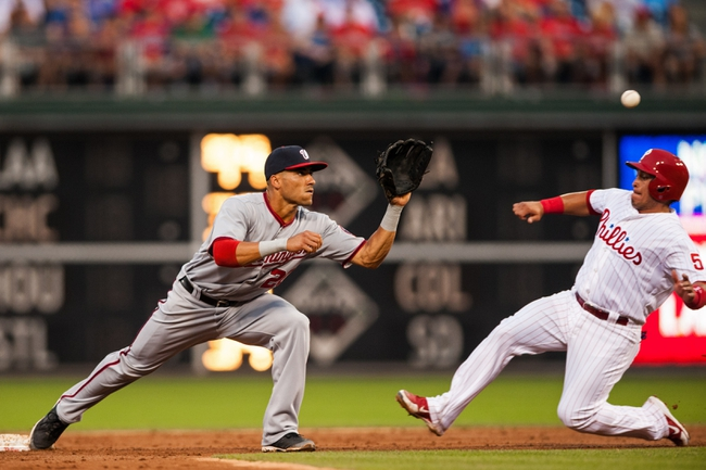 Jul 10, 2013; Philadelphia, PA, USA; Washington Nationals shortstop Ian Desmond (20) stretches for the ball as Philadelphia Phillies catcher Carlos Ruiz (51) slides in during the third inning at Citizens Bank Park. The Nationals defeated the Phillies 5-1. Mandatory Credit: Howard Smith-USA TODAY Sports