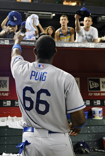Jul 10, 2013; Phoenix, AZ, USA;  Los Angeles Dodgers outfielder Yasiel Puig (66) signs autographs for fans after defeating the Arizona Diamondbacks in the 14th inning at Chase Field. The Dodgers defeated the Diamondbacks 7-5 in extra innings. Mandatory Credit: Jennifer Stewart-USA TODAY Sports