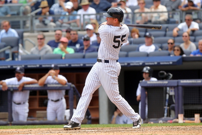 Jul 11, 2013; Bronx, NY, USA; New York Yankees first baseman Lyle Overbay (55) hits a two-RBI single against the Kansas City Royals during the fifth inning of a game at Yankee Stadium. Mandatory Credit: Brad Penner-USA TODAY Sports