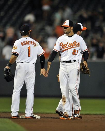 Jul 11, 2013; Baltimore, MD, USA; Baltimore Orioles teammates Brian Roberts (1) and Nick Markakis (21) celebrate after a game against the Texas Rangers at Oriole Park at Camden Yards. The Orioles defeated the Rangers 3-1. Mandatory Credit: Joy R. Absalon-USA TODAY Sports