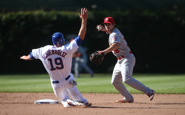 Jul 12, 2013; Chicago, IL, USA; St. Louis Cardinals shortstop Pete Kozma (38) turns a double play over Chicago Cubs right fielder Nate Schierholtz (19) during the sixth inning at Wrigley Field. Mandatory Credit: Jerry Lai-USA TODAY Sports