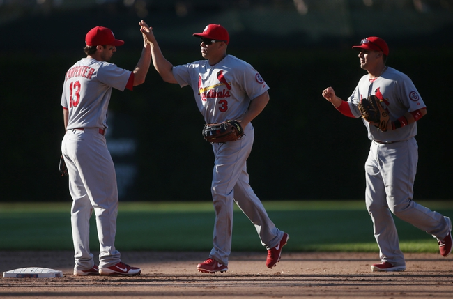 Jul 12, 2013; Chicago, IL, USA; St. Louis Cardinals players Matt Carpenter (13) , Carlos Beltran (3) and Allen Craig (21) celebrate after the game against the Chicago Cubs at Wrigley Field. The Cardinals won 3-2. Mandatory Credit: Jerry Lai-USA TODAY Sports