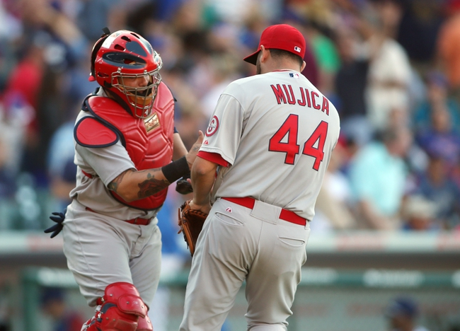Jul 12, 2013; Chicago, IL, USA; St. Louis Cardinals relief pitcher Edward Mujica (44) celebrates with catcher Yadier Molina after the game against the Chicago Cubs at Wrigley Field. The Cardinals won 3-2. Mandatory Credit: Jerry Lai-USA TODAY Sports