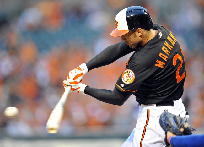 Jul 12, 2013; Baltimore, MD, USA; Baltimore Orioles right fielder Nick Markakis (21) singles in the third inning against the Toronto Blue Jays at Oriole Park at Camden Yards. Mandatory Credit: Joy R. Absalon-USA TODAY Sports
