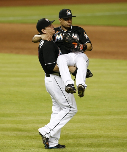 Jul 12, 2013; Miami, FL, USA; Miami Marlins first baseman Logan Morrison (left) picks up third baseman Placido Polanco (30) after defeating the Washington Nationals 8-3 at Marlins Park.  Mandatory Credit: Robert Mayer-USA TODAY Sports