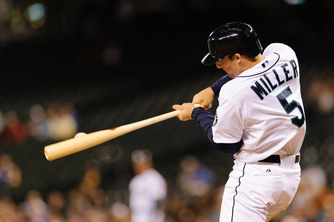 Jul 10, 2013; Seattle, WA, USA; Seattle Mariners shortstop Brad Miller (5) hits the ball during the game against the Boston Red Sox at Safeco Field. Boston defeated Seattle 11-4. Mandatory Credit: Steven Bisig-USA TODAY Sports