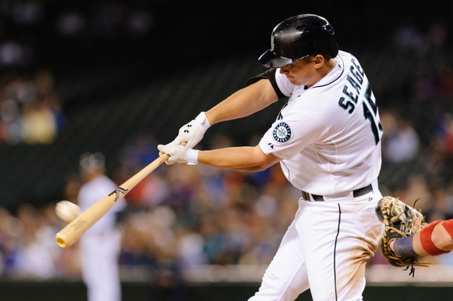 Jul 10, 2013; Seattle, WA, USA; Seattle Mariners third baseman Kyle Seager (15) hits the ball during the game against the Boston Red Sox at Safeco Field. Boston defeated Seattle 11-4. Mandatory Credit: Steven Bisig-USA TODAY Sports