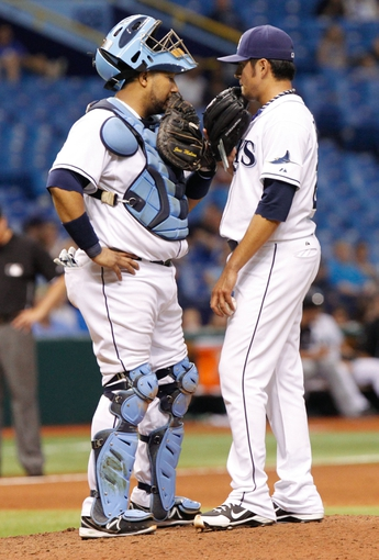 Jul 5, 2013; St. Petersburg, FL, USA; Tampa Bay Rays catcher Jose Molina (28) and relief pitcher Cesar Ramos (27) talk on the mound against the Chicago White Sox at Tropicana Field. Tampa Bay Rays defeated the Chicago White Sox 8-3. Mandatory Credit: Kim Klement-USA TODAY Sports