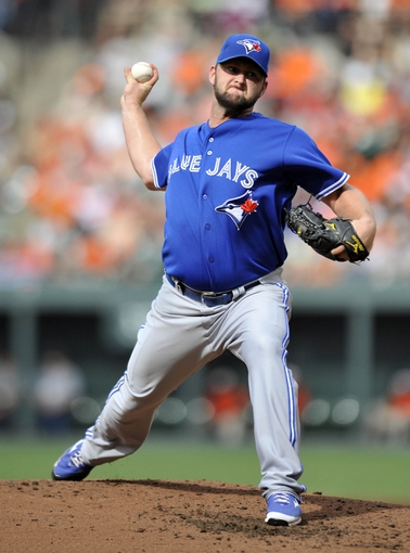 Jul 13, 2013; Baltimore, MD, USA; Toronto Blue Jays starting pitcher Todd Redmond (58) throws in the third inning against the Baltimore Orioles at Oriole Park at Camden Yards. Mandatory Credit: Joy R. Absalon-USA TODAY Sports