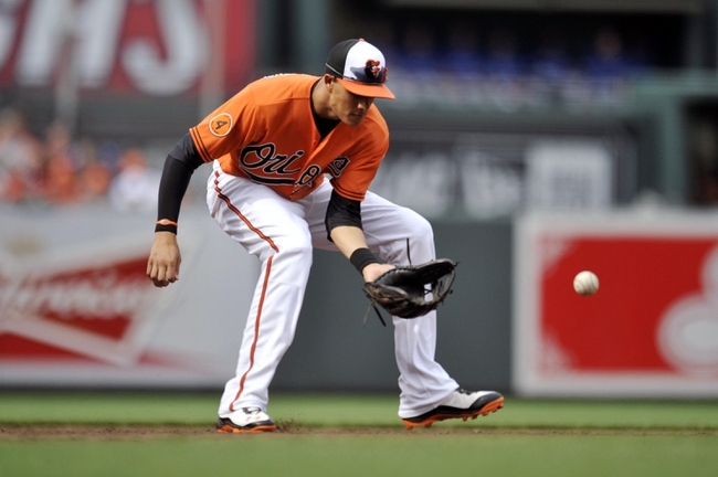 Jul 13, 2013; Baltimore, MD, USA; Baltimore Orioles third baseman Manny Machado (13) fields a ground ball hit by Toronto Blue Jays right fielder Jose Bautista (not shown) in the third inning at Oriole Park at Camden Yards. Mandatory Credit: Joy R. Absalon-USA TODAY Sports