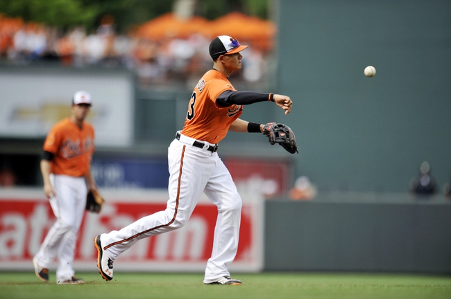 Jul 13, 2013; Baltimore, MD, USA; Baltimore Orioles third baseman Manny Machado (13) throws over to first base to get out Toronto Blue Jays right fielder Jose Bautista (not shown) in the third inning at Oriole Park at Camden Yards. Mandatory Credit: Joy R. Absalon-USA TODAY Sports