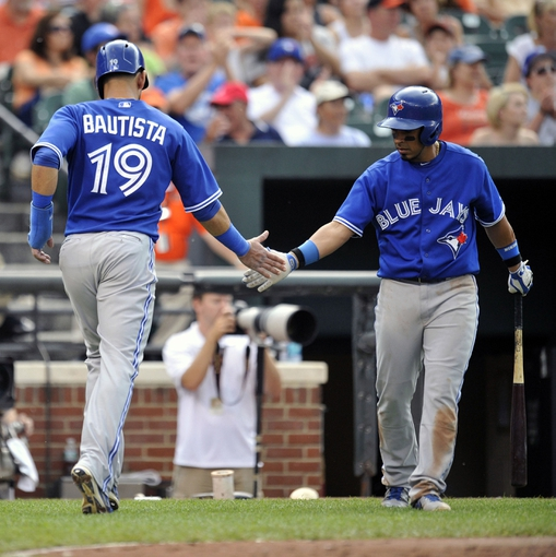 Jul 13, 2013; Baltimore, MD, USA; Toronto Blue Jays right fielder Jose Bautista (19) is congratulated by Toronto Blue Jays second baseman Maicer Izturis (3) after scoring on one-run rbi single by Colby Rasmus (not shown) in the seventh inning against the Baltimore Orioles at Oriole Park at Camden Yards. The Blue Jays defeated the Orioles 7-3. Mandatory Credit: Joy R. Absalon-USA TODAY Sports