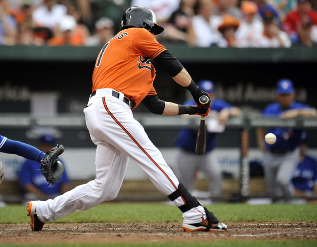 Jul 13, 2013; Baltimore, MD, USA; Baltimore Orioles right fielder Nick Markakis (21) singles in the eighth inning against the Toronto Blue Jays at Oriole Park at Camden Yards. The Blue Jays defeated the Orioles 7-3. Mandatory Credit: Joy R. Absalon-USA TODAY Sports