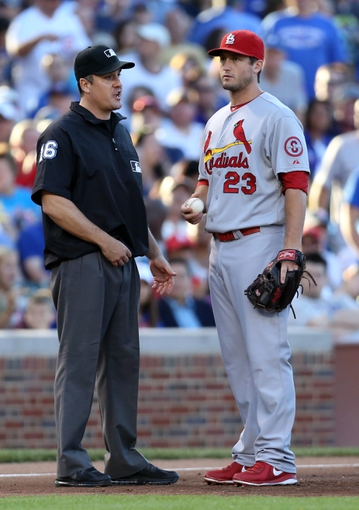 Jul 13, 2013; Chicago, IL, USA; Third base umpire Mike DiMuro (16) discusses the catcher interference call with St. Louis Cardinals third baseman David Freese (23) during the second inning against the Chicago Cubs at Wrigley Field. Mandatory Credit: Dennis Wierzbicki-USA TODAY Sports