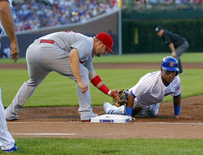 Jul 13, 2013; Chicago, IL, USA; Chicago Cubs right fielder Dave Sappelt (17) slides under the tag of St. Louis Cardinals first baseman Matt Adams (53) during the second inning at Wrigley Field. Mandatory Credit: Dennis Wierzbicki-USA TODAY Sports