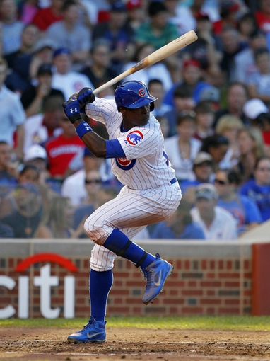 Jul 13, 2013; Chicago, IL, USA; Chicago Cubs left fielder Alfonso Soriano (12) hits a solo home run during the third inning against the St. Louis Cardinals at Wrigley Field. Mandatory Credit: Dennis Wierzbicki-USA TODAY Sports