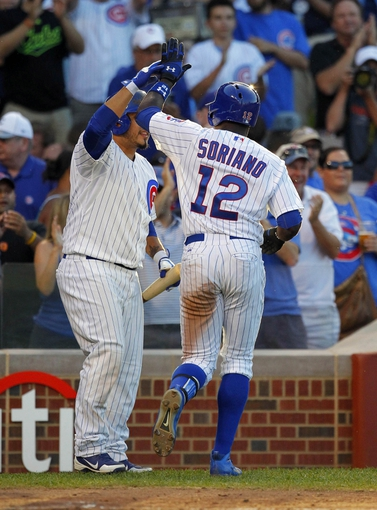 Jul 13, 2013; Chicago, IL, USA; Chicago Cubs left fielder Alfonso Soriano (12) is congratulated for hitting a home run by catcher Dioner Navarro (30) during the third inning against the St. Louis Cardinals at Wrigley Field. Mandatory Credit: Dennis Wierzbicki-USA TODAY Sports