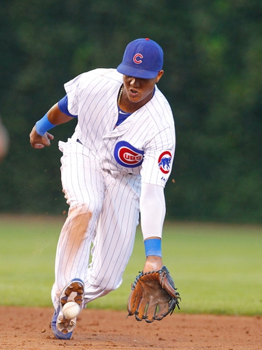 Jul 13, 2013; Chicago, IL, USA; Chicago Cubs shortstop Starlin Castro (13) fields a ground ball off the bat of St. Louis Cardinals first baseman Allen Craig (not pictured) during the fifth inning at Wrigley Field. Mandatory Credit: Dennis Wierzbicki-USA TODAY Sports