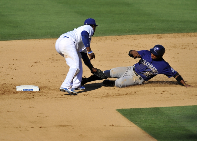 July 13, 2013; Los Angeles, CA, USA; Colorado Rockies shortstop Jonathan Herrera (18) is caught stealing second against the tag of Los Angeles Dodgers shortstop Hanley Ramirez (13) during the sixth inning at Dodger Stadium. Mandatory Credit: Gary A. Vasquez-USA TODAY Sports