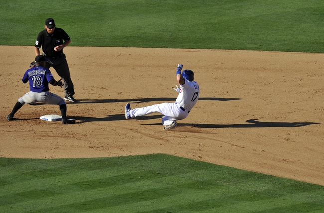 July 13, 2013; Los Angeles, CA, USA; Los Angeles Dodgers catcher A.J. Ellis (17) reaches second reaches second safely against the tag of Colorado Rockies shortstop Jonathan Herrera (18) after hitting a double during the seventh inning at Dodger Stadium. Mandatory Credit: Gary A. Vasquez-USA TODAY Sports