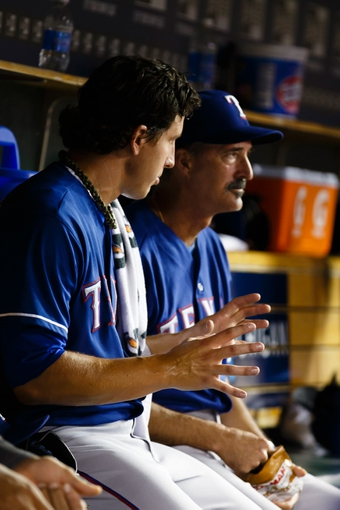 July 13, 2013; Detroit, MI, USA; Texas Rangers starting pitcher Derek Holland (45) talks to pitching coach Mike Maddux (31) in the dugout during the eighth inning against the Detroit Tigers at Comerica Park. Mandatory Credit: Rick Osentoski-USA TODAY Sports