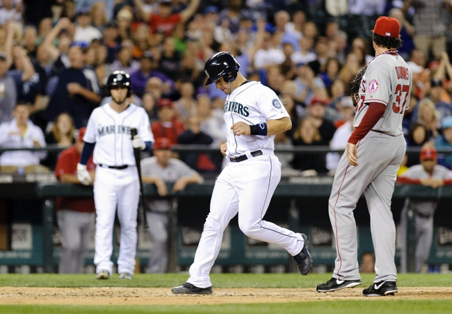 Jul 13, 2013; Seattle, WA, USA; Seattle Mariners catcher Mike Zunino (3) scores a run off a wild pitch thrown by Los Angeles Angels relief pitcher Scott Downs (37) during the 7th inning at Safeco Field. Mandatory Credit: Steven Bisig-USA TODAY Sports