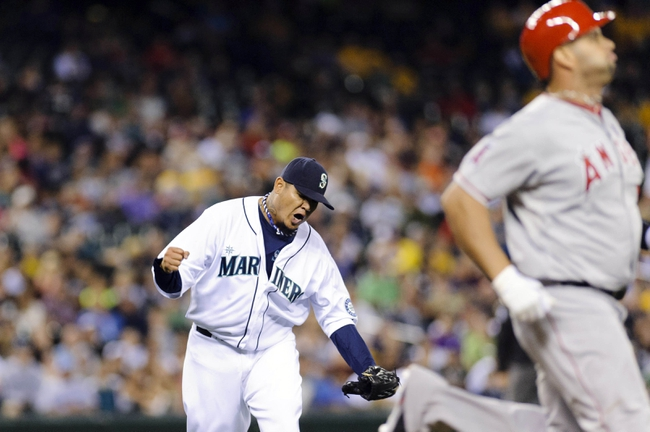 Jul 13, 2013; Seattle, WA, USA; Seattle Mariners starting pitcher Felix Hernandez (34) reacts to Los Angeles Angels designated hitter Albert Pujols (5) being thrown out at 1st base for the final out of the 8th inning at Safeco Field. Mandatory Credit: Steven Bisig-USA TODAY Sports