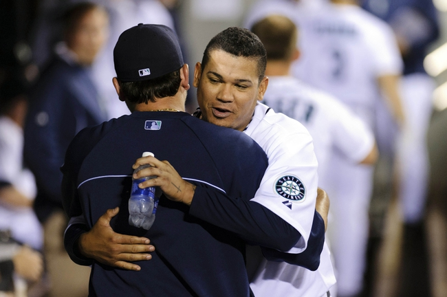 Jul 13, 2013; Seattle, WA, USA; Seattle Mariners starting pitcher Felix Hernandez (34) hugs Seattle Mariners starting pitcher Joe Saunders (23) during the 8th inning against the Los Angeles Angels at Safeco Field. Mandatory Credit: Steven Bisig-USA TODAY Sports